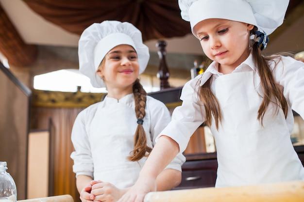 Dos chicas hacen masa de harina. Foto Premium