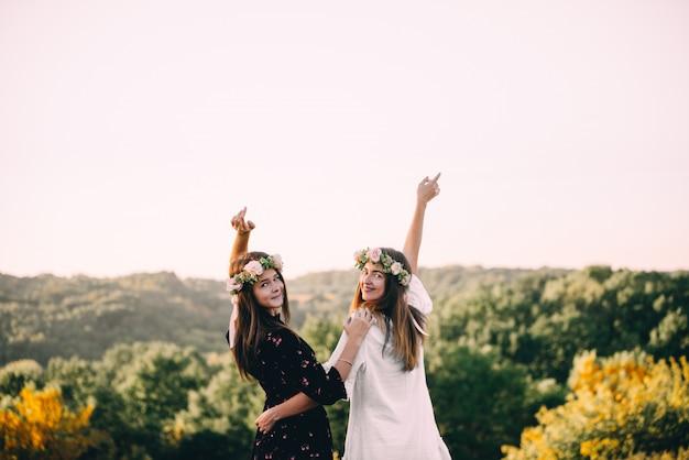 Dos chicas jóvenes se abrazan durante la puesta de sol en el campo con concepto de amistad de copas de vino Foto Premium