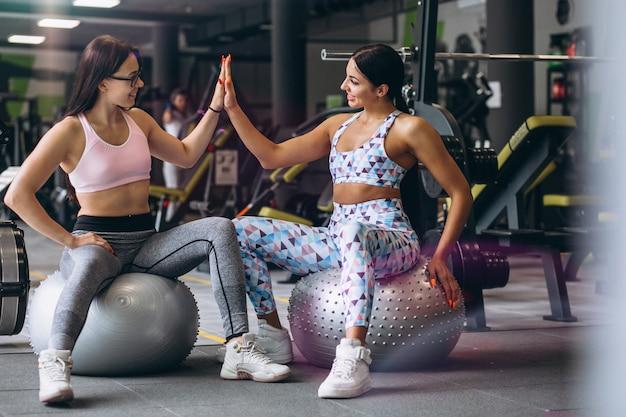 Dos chicas jóvenes entrenando en el gimnasio sentado en la bola de la aptitud Foto gratis