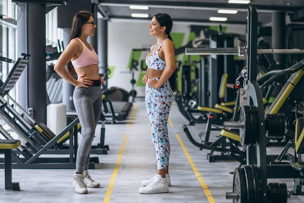 Dos chicas jóvenes entrenando juntas en el gimnasio Foto gratis
