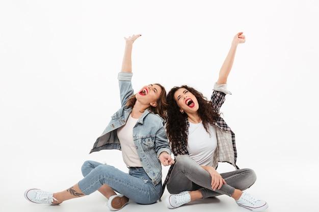 Dos chicas jóvenes sentados juntos en el suelo mientras gritaban y miraban por encima de la pared blanca Foto gratis