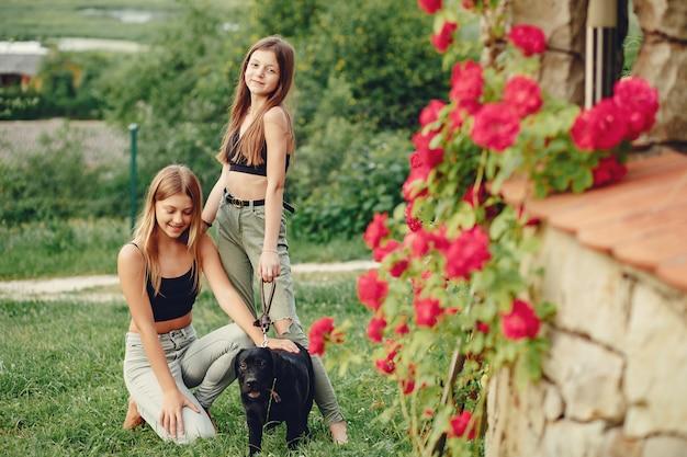 Dos chicas lindas en un parque de verano con un perro Foto gratis