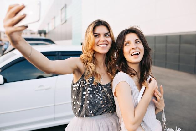 Dos chicas muy de moda haciendo selfie-retrato en el estacionamiento. Foto gratis