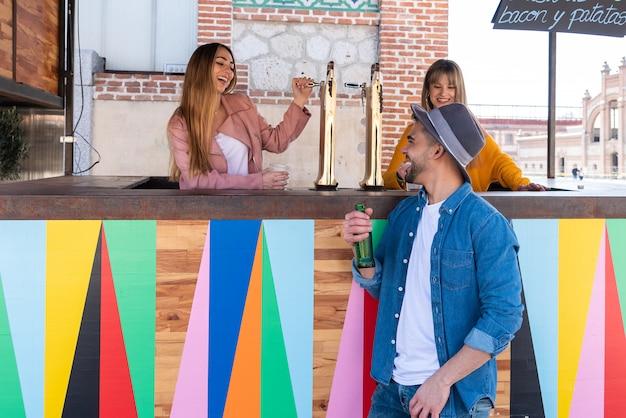 Dos chicas que trabajan en un bar al aire libre brindan y celebran con un cliente Foto Premium