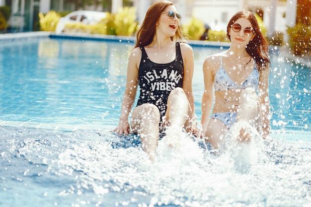 Dos chicas riendo y divirtiéndose junto a la piscina Foto gratis