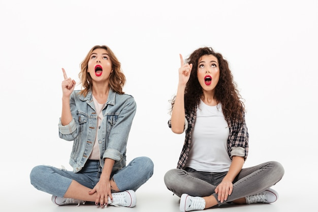 Dos chicas sorprendidas sentadas juntas en el piso mientras señalan y miran con la boca abierta sobre la pared blanca Foto gratis