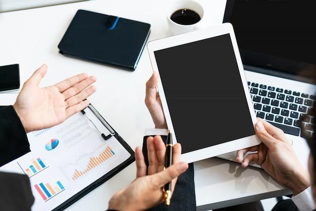 Dos colegas que discuten datos con la tableta en la tabla del escritorio en oficina. cierre de análisis de equipo de negocios y concepto de estrategia. Foto Premium