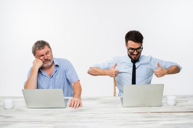 Dos colegas que trabajan juntos en la oficina en blanco Foto gratis