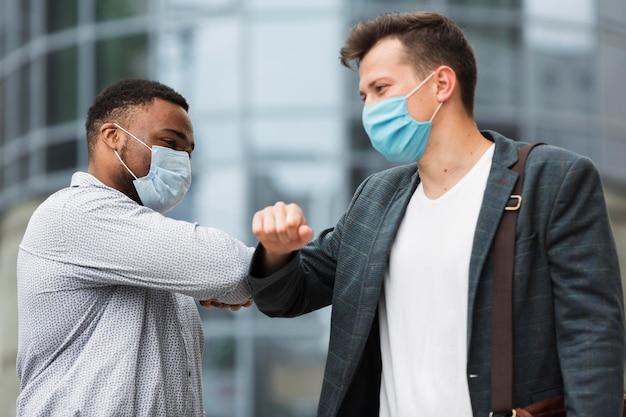 Dos colegas tocándose los codos al aire libre durante la pandemia Foto gratis