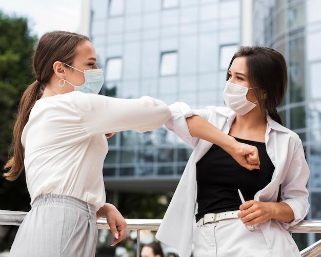 Dos compañeros de trabajo tocándose los codos al aire libre durante la pandemia mientras usan máscaras Foto gratis
