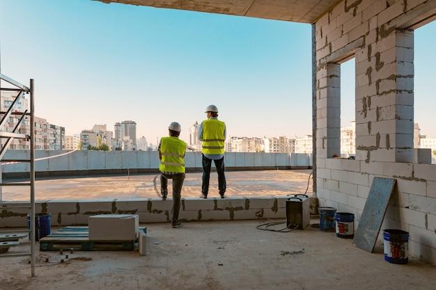 Dos constructores masculinos en el sitio de construcción Foto Premium