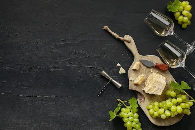 Dos copas de vino blanco y un sabroso plato de queso con fruta en un plato de cocina de madera sobre piedra negra Foto gratis