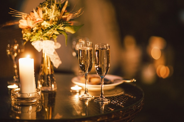 Dos copas de vino en la mesa en el fondo del ramo de la boda, noche, fin del evento Foto Premium