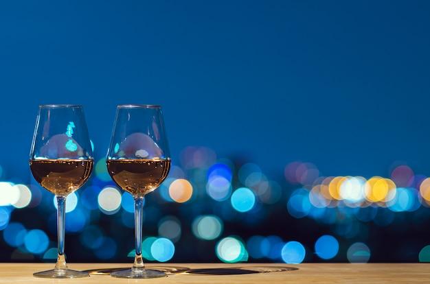 Dos copas de vino rosado con la luz colorida de la ciudad del bokeh del edificio de la azotea. Foto Premium