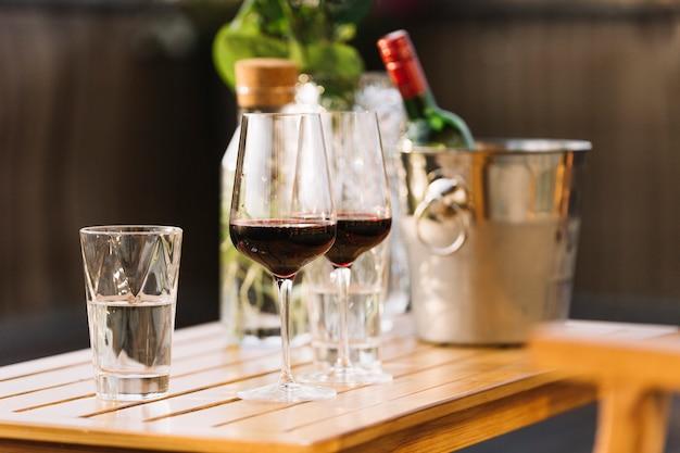 Dos copas de vino tinto y vaso de agua en la mesa de madera Foto gratis