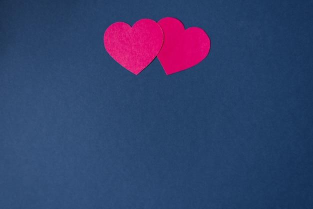 Dos corazones de color rosa sobre un fondo azul oscuro con copia. patrón para el día de san valentín. tarjeta navideña para el día del amor. origami Foto Premium