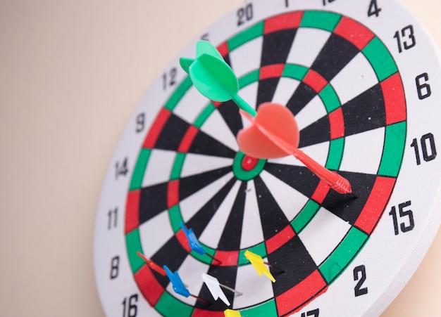 Dos dardos en el tablero de dardos en la pared Foto Premium