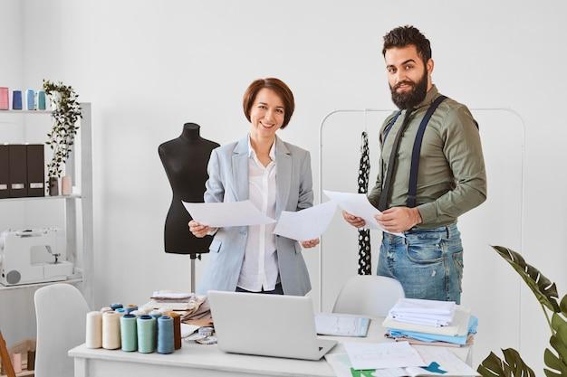 Dos diseñadores de moda posando en atelier con planes de línea de ropa Foto gratis