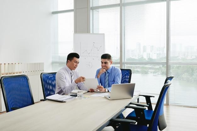 Dos ejecutivos de negocios negociando el contrato en la sala de conferencias. Foto gratis