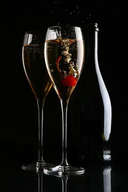 Dos elegantes copas con champagne y cereza. Foto gratis