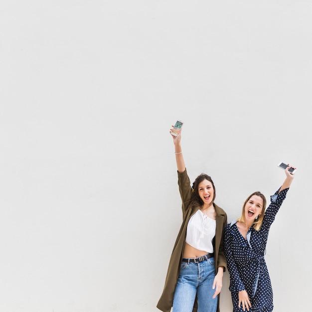 Dos elegantes excitaron a la mujer que levantaba su mano que sostenía el teléfono móvil contra el fondo blanco Foto gratis