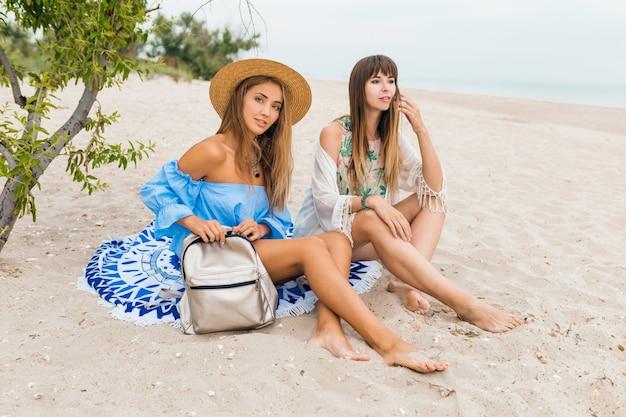 Dos elegantes mujeres muy sonrientes sentadas en la arena en las vacaciones de verano en la playa tropical, amigos viajan juntos Foto gratis