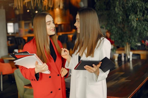 Dos empresarias trabajando en una cafetería Foto gratis