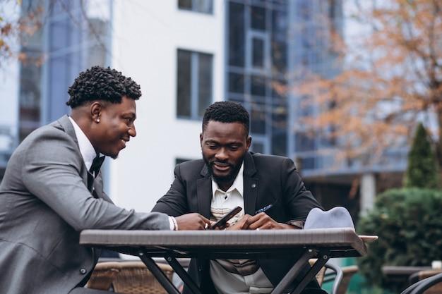 Dos empresario africano sentado fuera de café Foto gratis