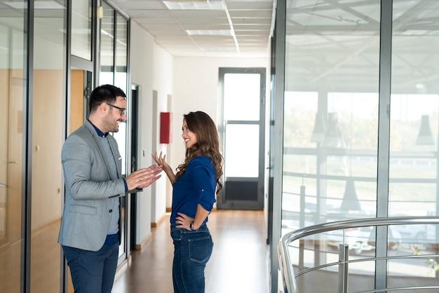 Dos empresarios conversando en el pasillo corporativo de la oficina. Foto Premium