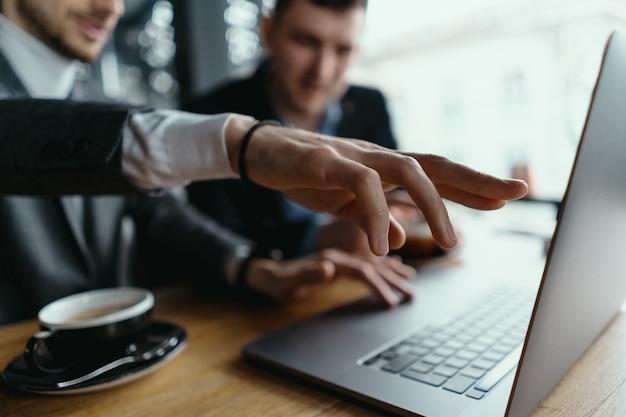 Dos empresarios señalando la pantalla del portátil mientras discuten Foto gratis