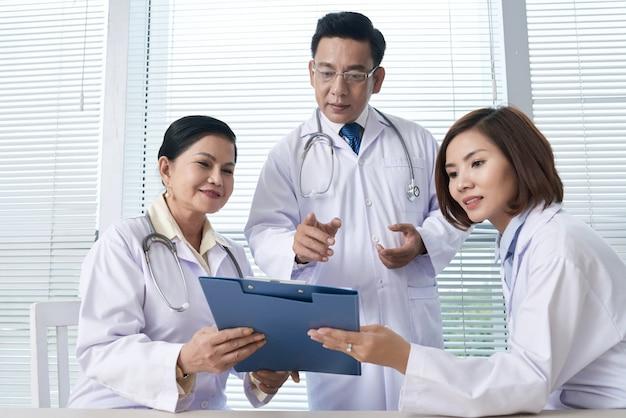 Dos enfermeras que informan al médico jefe. Foto gratis