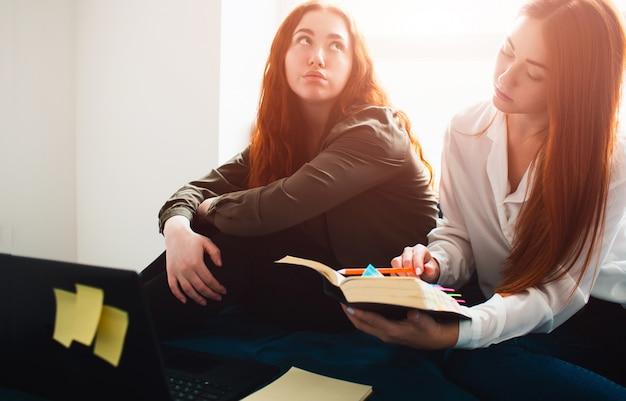 Dos estudiantes pelirrojos estudian en casa o en un dormitorio estudiantil. se preparan para los exámenes. una mujer joven está aburrida, y el segundo estudiante está enfocado en estudiar. Foto Premium