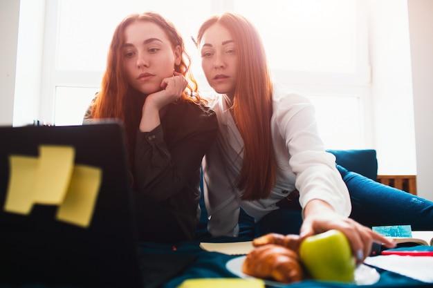 Dos estudiantes pelirrojos estudian en casa o se preparan para los exámenes. las mujeres jóvenes haciendo los deberes en una cama dormitorio cerca de la ventana. hay cuadernos, libros de comida, una tableta y una computadora portátil y documentos Foto Premium