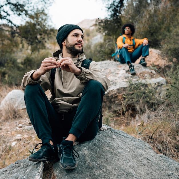 Dos excursionista masculino sentado en la roca Foto gratis