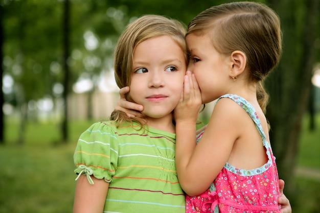 Dos gemelas hermanitas susurran al oído Foto Premium