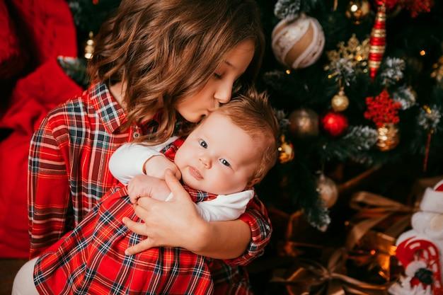 Dos hermanas se abrazan junto a un árbol de navidad Foto Premium