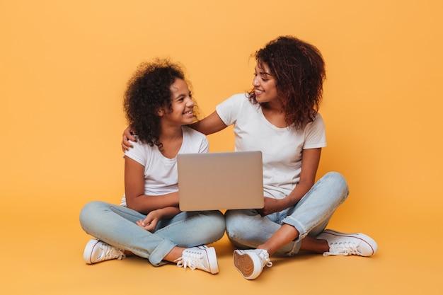 Dos hermanas afroamericanas alegres con ordenador portátil Foto gratis