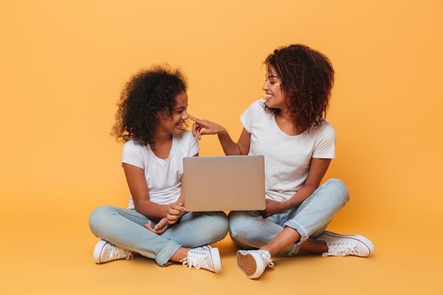 Dos hermanas afroamericanas sonrientes que sostienen la computadora portátil Foto gratis