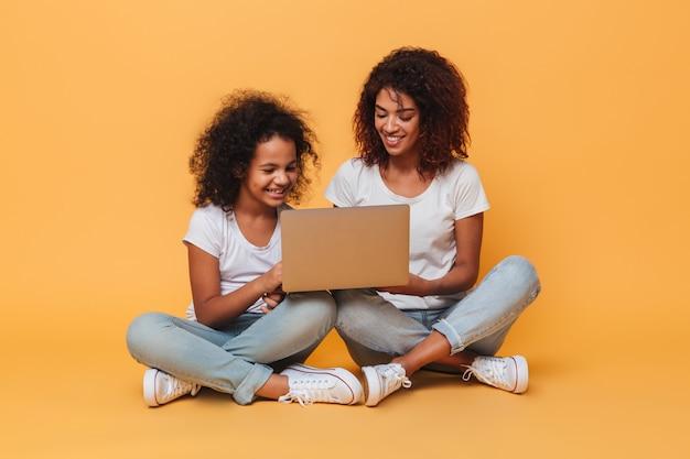 Dos hermanas afroamericanas sonrientes usando la computadora portátil mientras está sentado Foto gratis