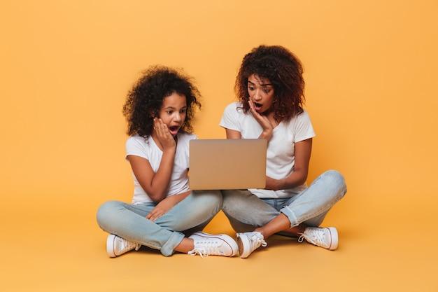 Dos hermanas afroamericanas sorprendidas usando la computadora portátil Foto gratis