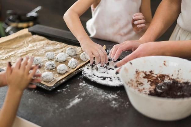 Dos hermanas y madre preparando galletas de chocolate en la cocina Foto gratis