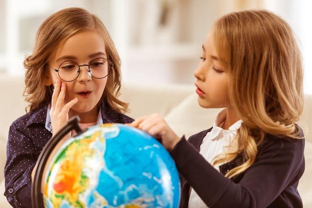 Dos hermosas chicas con chaquetas oscuras consideran el globo. Foto Premium