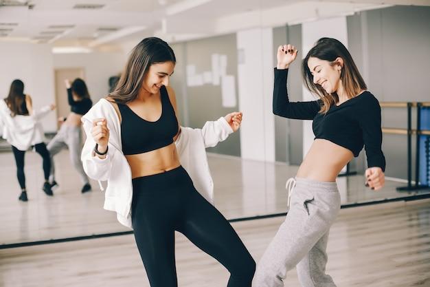 Dos hermosas chicas esbeltas haciendo baile y gimnasia en el salón de baile Foto gratis