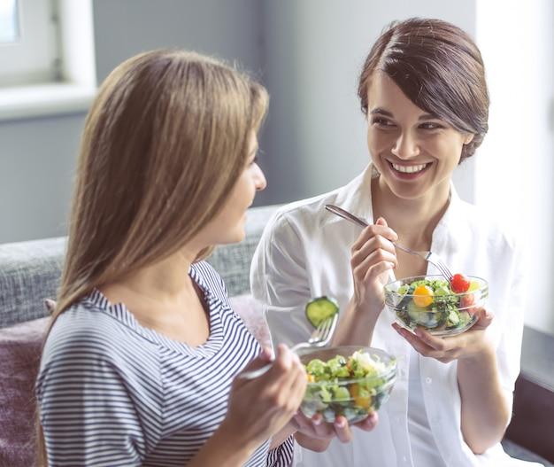 Dos hermosas chicas están comiendo ensalada. Foto Premium