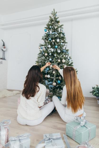 8039afacc3 Dos hermosas chicas están decorando un árbol de navidad. Foto Premium