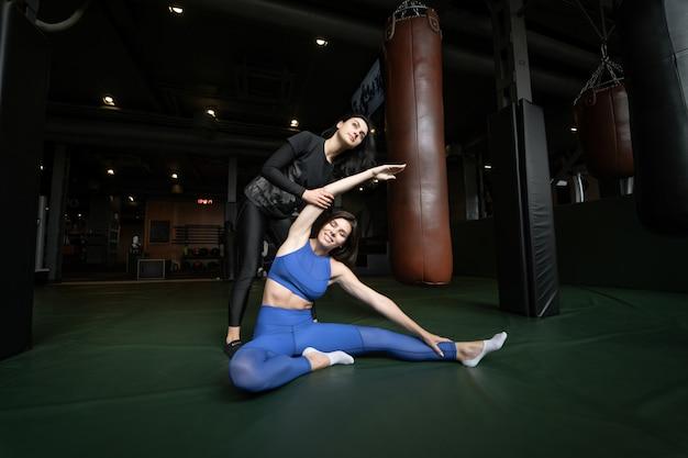 Dos hermosas chicas jóvenes haciendo fitness en un gimnasio. estirar los músculos de las piernas y los brazos. Foto gratis