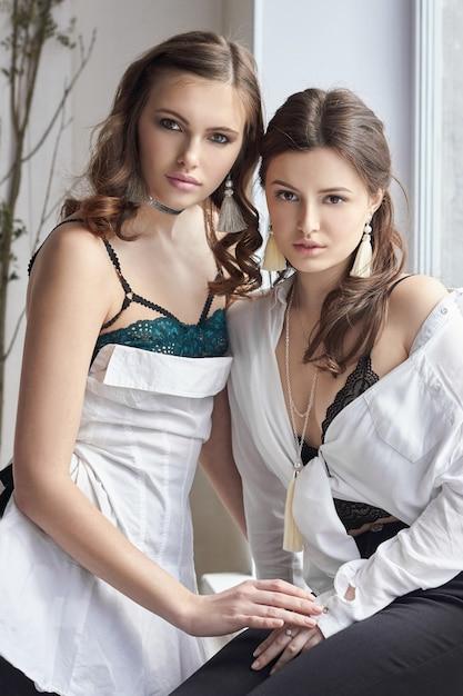 Dos Hermosas Chicas En Ropa Interior Sentada En La Ventana