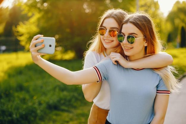 Dos hermosas muchachas hermosas jóvenes con pelo rubio brillante y una falda y caminar Foto gratis