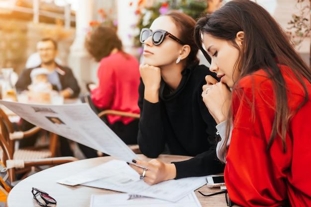Dos hermosas mujeres con estilo sentado a la mesa en la calle cafe Foto gratis