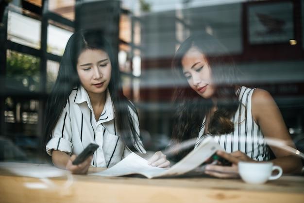 Dos hermosas mujeres hablando todo juntos en la cafetería cafetería Foto gratis